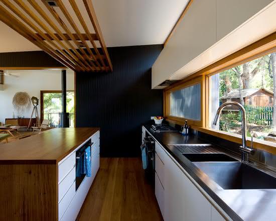 Cozinha com ilha branca, preta e com madeira.