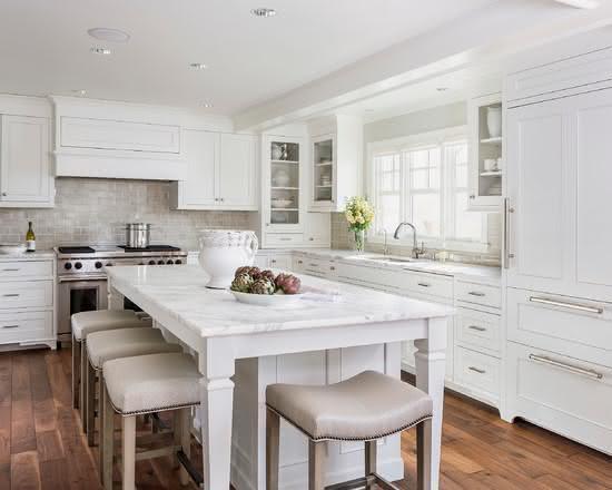 Cozinha toda branca, com ilha central.