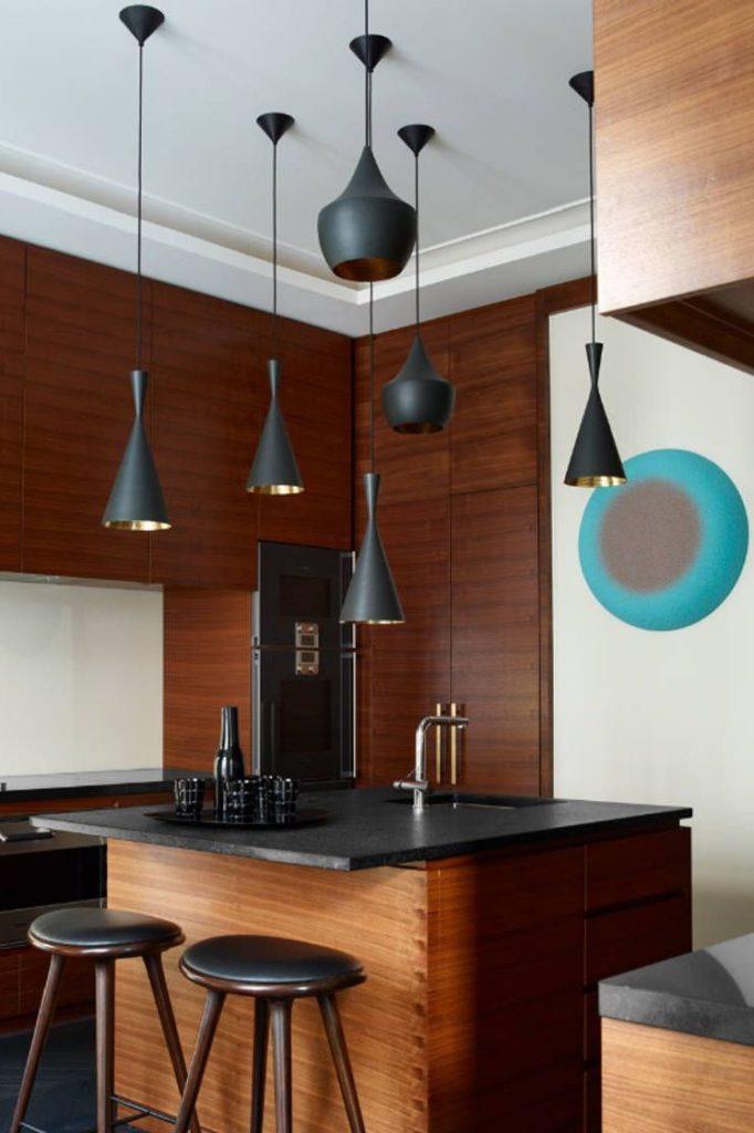 Cozinha de ilha com várias luminárias.