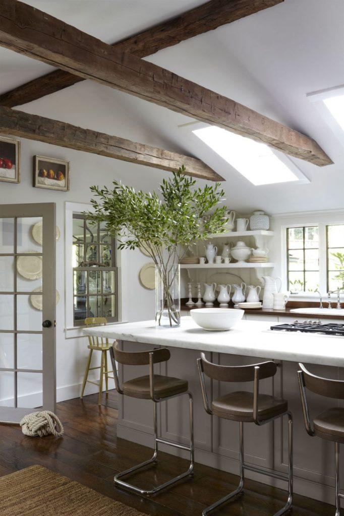 Cozinha branca com teto de madeira.