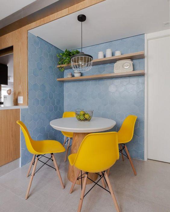 Sala de jantar traz azul na parede e amarelo nas cadeiras.