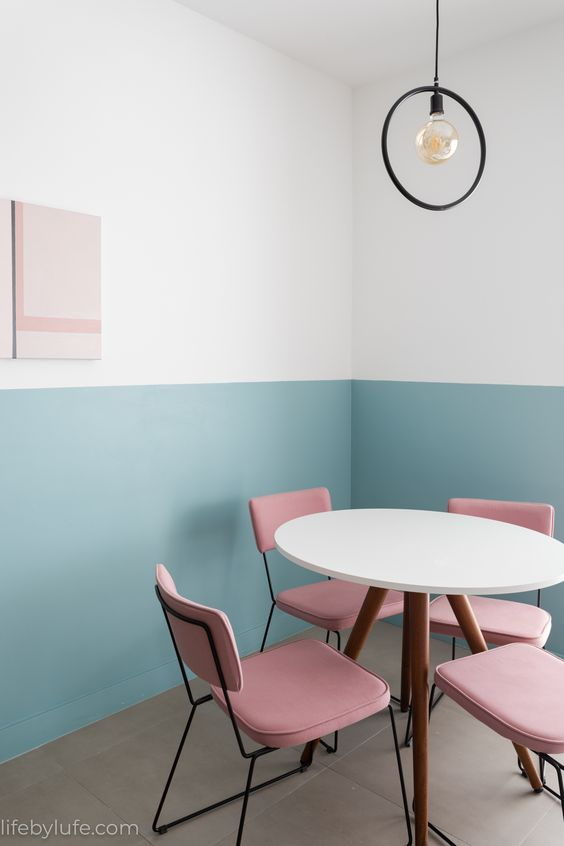 Meia parede em azul e cadeiras rosa.