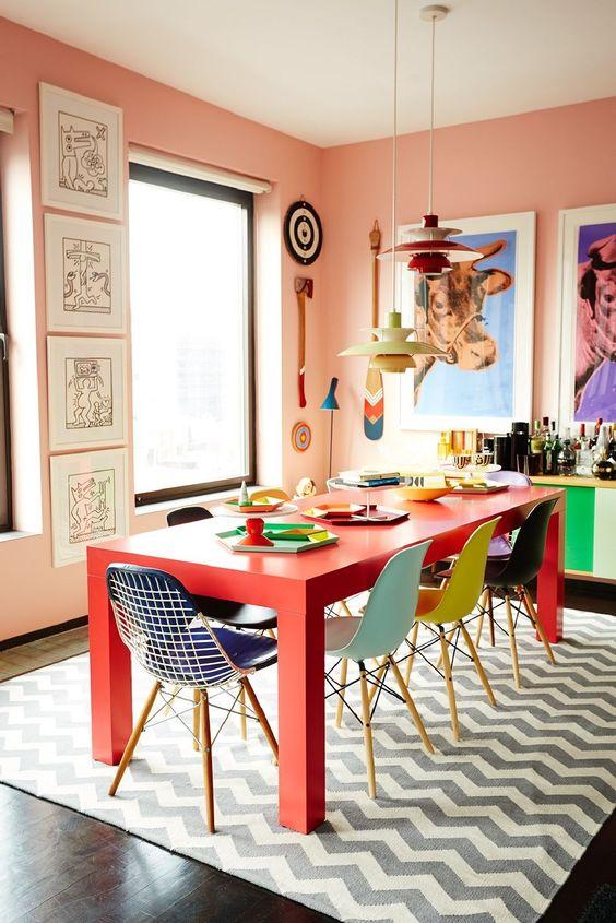 Sala de jantar supercolorida com mesa vermelha, parede rose e cadeiras em diferentes cores.