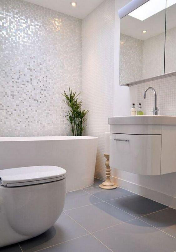 Banheiro todo branco, com pastilhas em tons de branco e cinza.