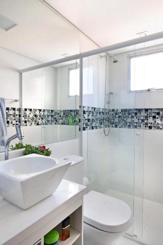 Banheiro branco com a instalação de pastilhas na lateral do banheiro.