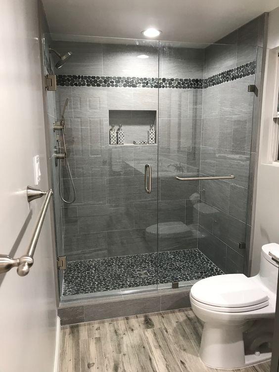 Banheiro moderno em tons de cinza escuro com pastilha do chão e na lateral da parede do box.