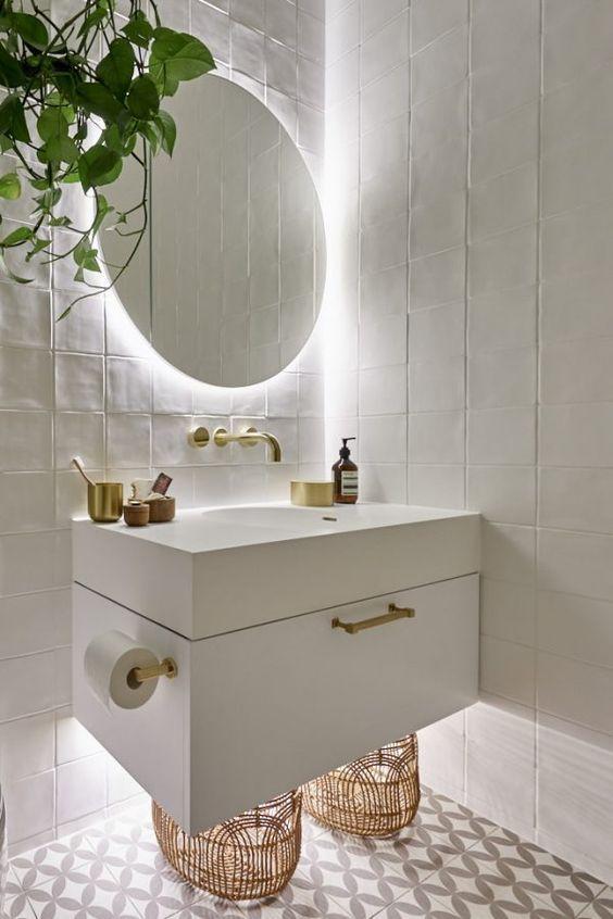 Banheiro planejado branco com metais em dourador e luz ao fundo do espelho.
