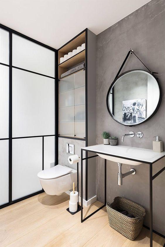 Paredes em tom de cinza e espelho oval deixa o ambiente moderno e industrial no banheiro planejado.