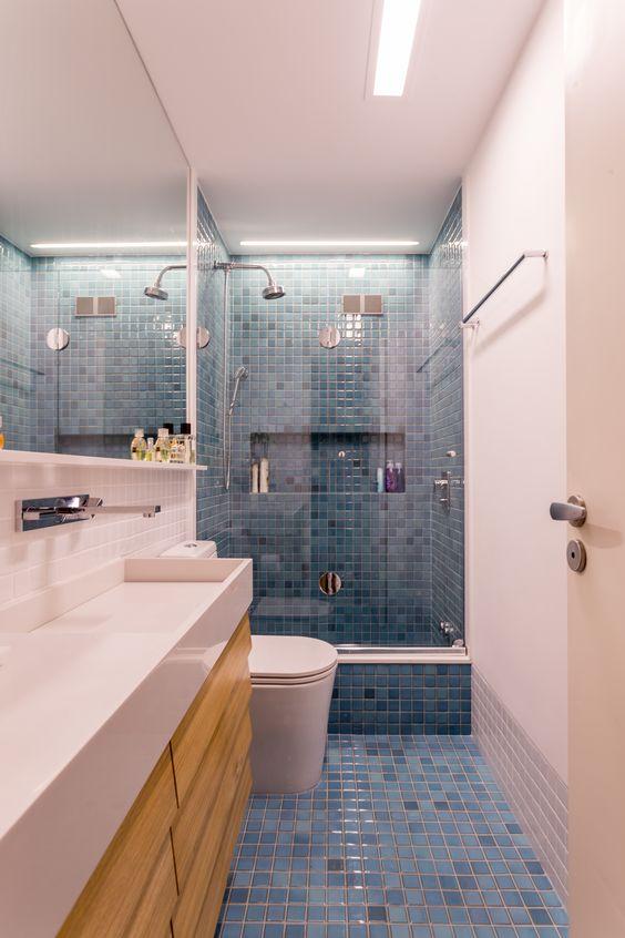 Pastilha em azul para banheiro planejado com gabinete em madeira. Banheiro e bancada em tons brancos.