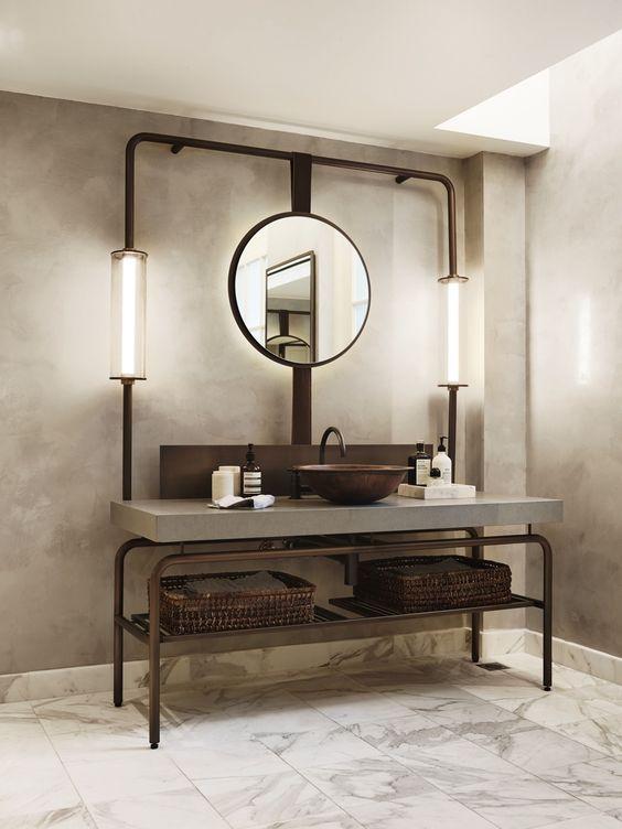 Banheiro moderno com metais em cor ferrugem, cuba sob a bancada deixa o ar industrial e contemporâneo.