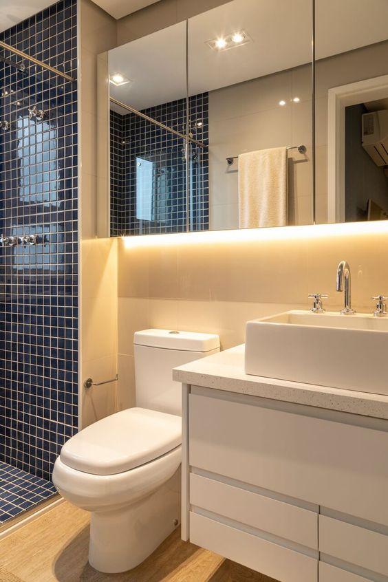 Banheiro planejado pequeno. Pastilhas em azul e  a luz por trás do espelho chama a atenção e deixa o ambiente aconchegante.