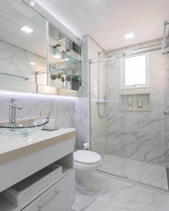 Banheiro com mármore totalmente clean. Luz por de traz do espelho chama a atenção. Bancada com cuba de vidro é minimalista.