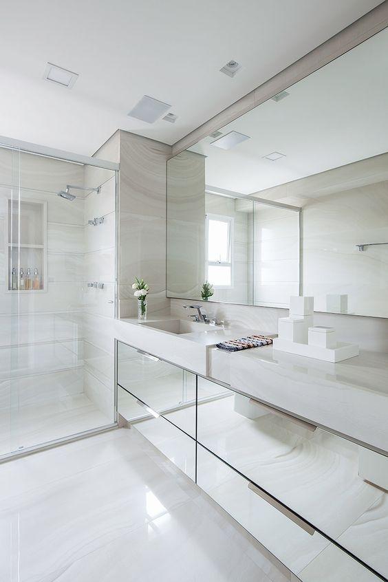 Espelho e bancada de vidros deixa o ambiente moderno e leve.