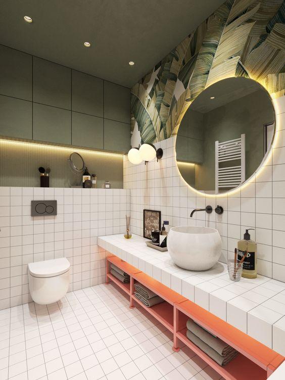 Espelho redondo em uma proposta criativa. Cuba sob a bancada.  Banheiro branco com detalhes em rosa.