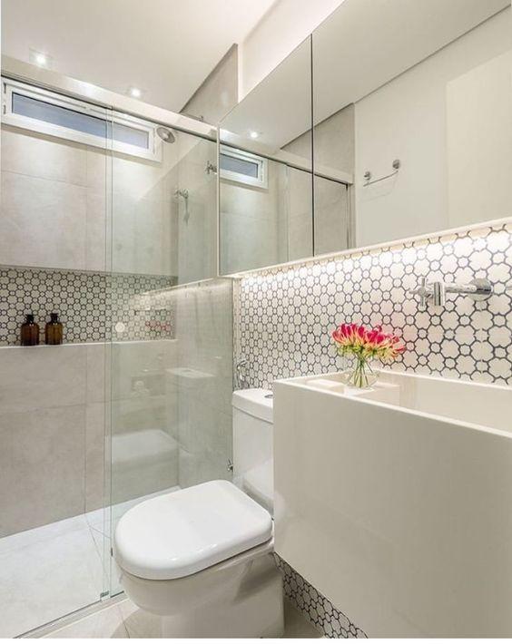Espelho retangular com duas portas em banheiro branco. Uma faixa com pastilha e uma cuba inteira da base até a altura da torneira.