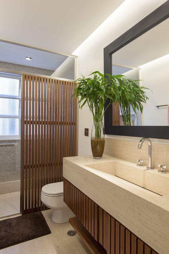 Banheiro elegante com mistura de vários elementos, como madeira, pastilha e mármore.