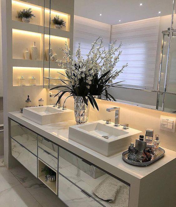 Ambiente elegante. Detalhe para as flores sob a bancada conferindo um banheiro luxuoso.