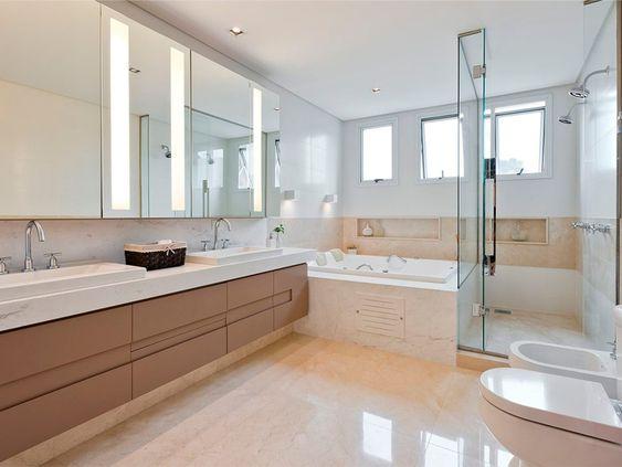 Banheiro planejado espaçoso com banheira, 2 cubas. Tons de marrom deixou o ambiente elegante.