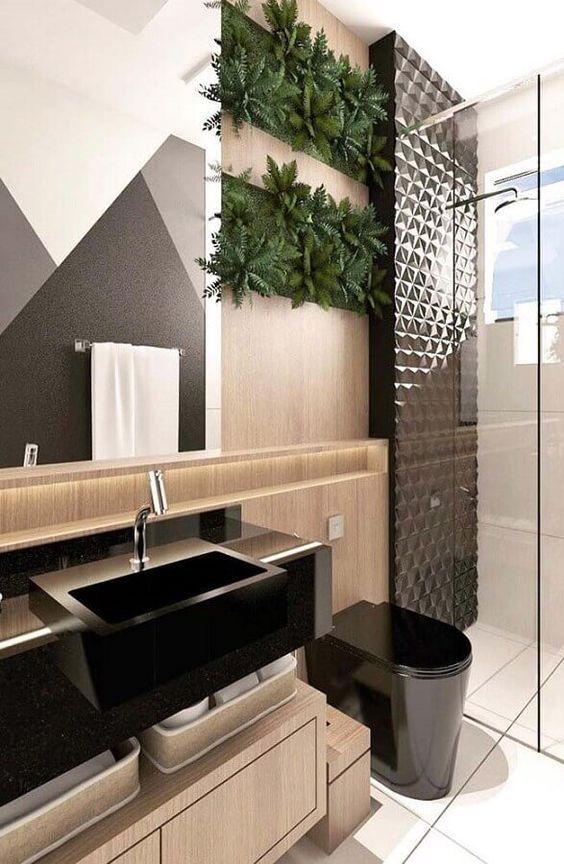 Banheiro planejado com revestimento em 3d e decoração com plantas na parede. bancada e vaso na cor preta.