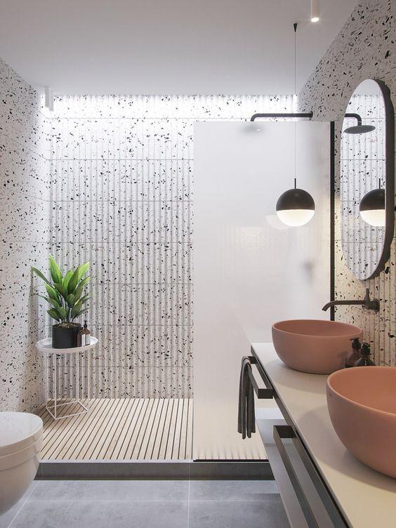 Banheiro claro com revestimento criativo. Cubas cor de rosa sob a bancada.