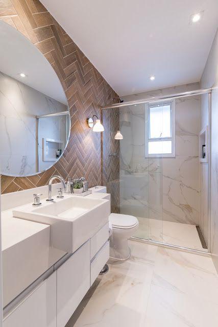 Banheiro planejado com revestimento em madeira no estilo de tijolinho. Vidro oval grande na parece.
