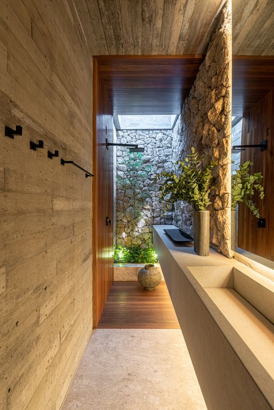 Banheiro planejado ultra moderno com pedras e madeiras.
