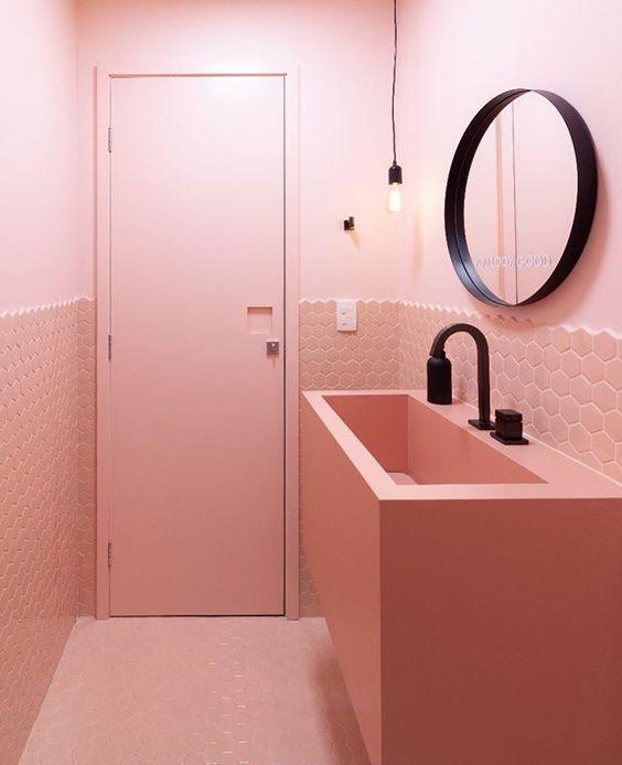 Banheiro pequeno e criativo na cor rosa e com metais na cor preta.