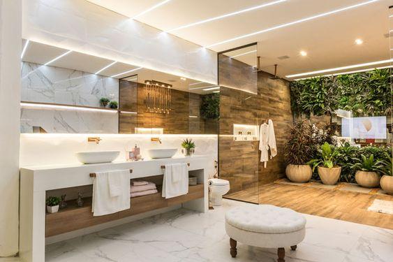 Banheiro planejado luxuoso com muitos detalhes em madeira, mármore e vidro. Plantas estão no ambiente.