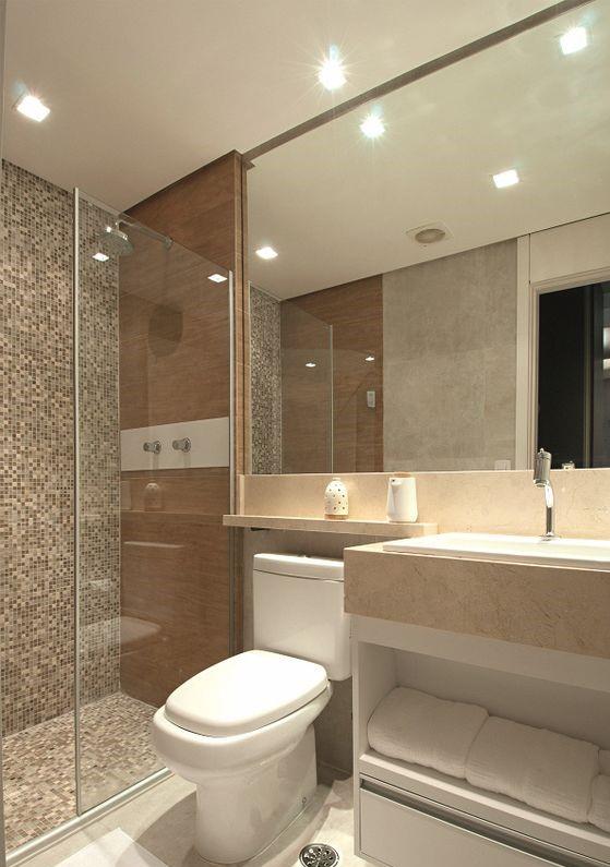Banheiro planejado e pequeno, com pastilhas marrons, douradas e brancas. Decorado com madeira, cimento e vidro.