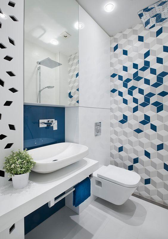 Banheiro moderno com revestimento geométrico na cor azul, cinza e branca.