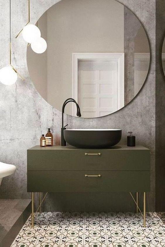 Banheiro planejado pequeno com ladrilhos no chão e cimento queimado na parede. O espelho chama a atenção pelo tamanho que é oval.
