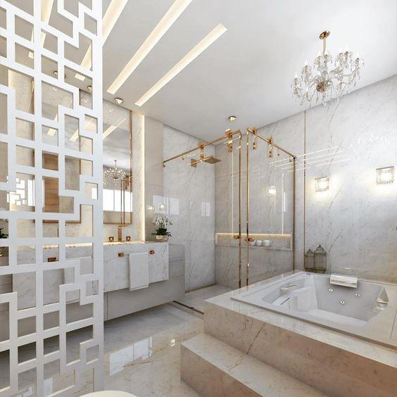 Banheiro planejado grande e luxuoso. Todo em mármore e metais dourados. A banheira é grande e o ambiente iluminado.