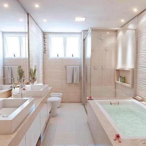 Banheiro planejado pequeno com banheira. Revestimento na cor creme deixa o ambiente limpo, clean e elegante.