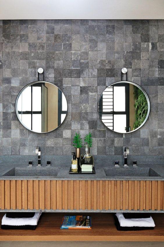 Revestimento na parede em pedra chama a atenção com duas cubas sob gabinete de madeira.  Há também dois espelhos ovais no estilo retrô.
