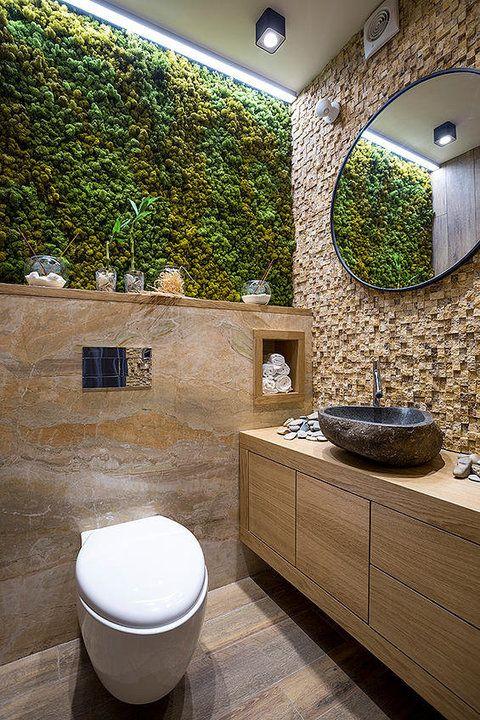 Banheiro pequeno com mescla de diversos revestimentos em pedra, mármore e musgo.