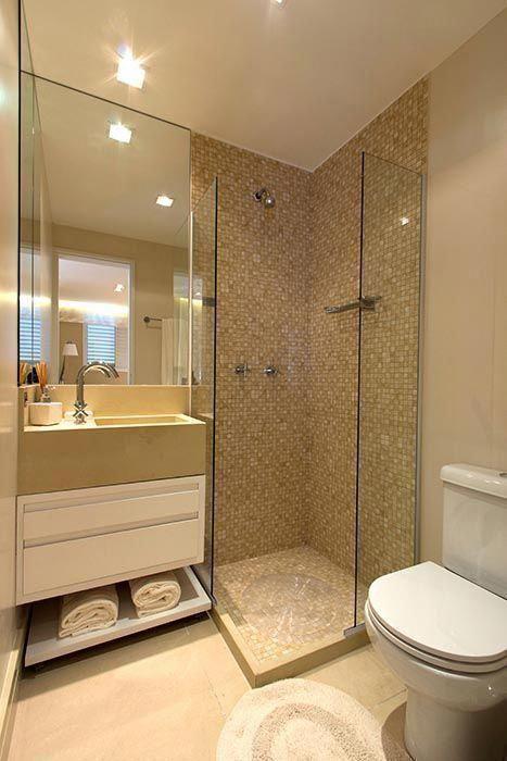 Banheiro planejado pequeno, em tons de creme com pastilhas douradas.