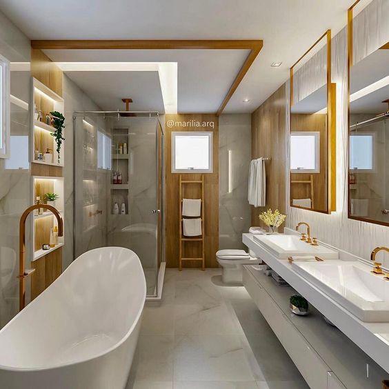Banheiro planejado feminino com revestimento branco e metais dourados.