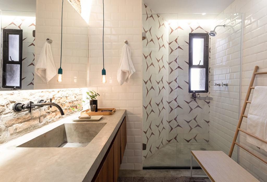 Banheiro pequeno com mistura de diversos revestimentos. Cuba em cimento queimado.