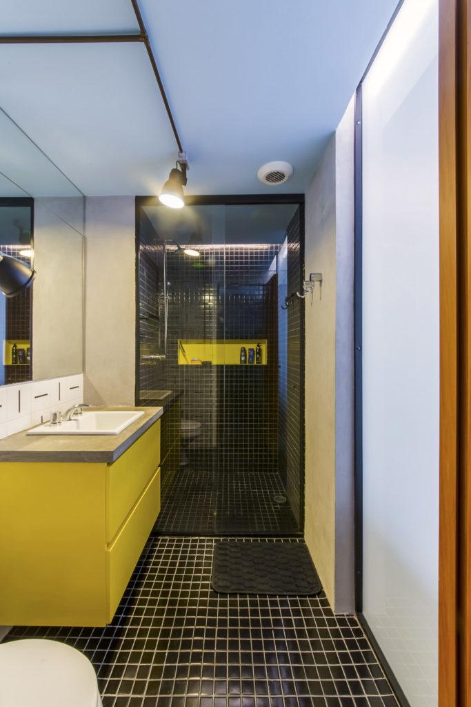 Banheiro com proposta jovem e moderna. Piso na cor preta e gabinete na cor amarela.