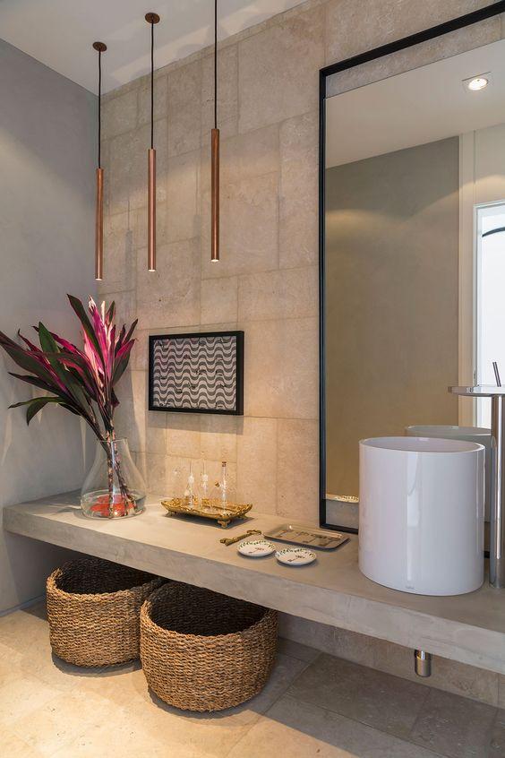Banheiro planejado pequeno com cuba diferenciada sob a bancada de cimento queimado.