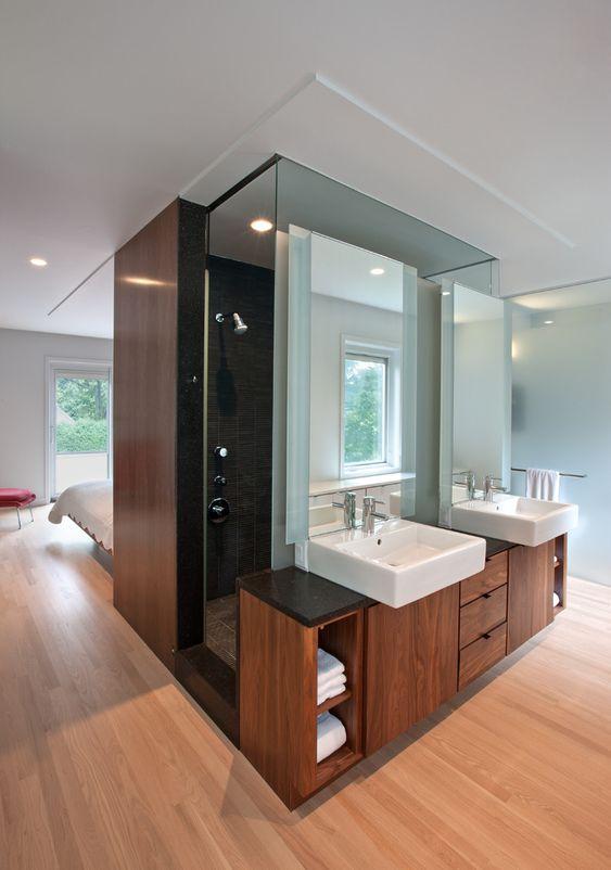 Banheiro separado do quarto por uma parede com duas cubas sob bancada de madeira.