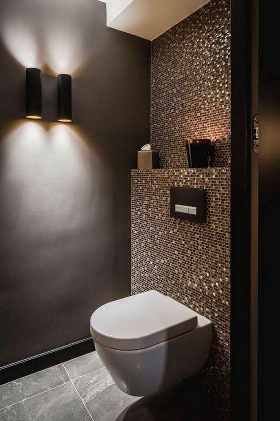 Banheiro planejado com pastilhas em tons escuros e com diversas texturas.