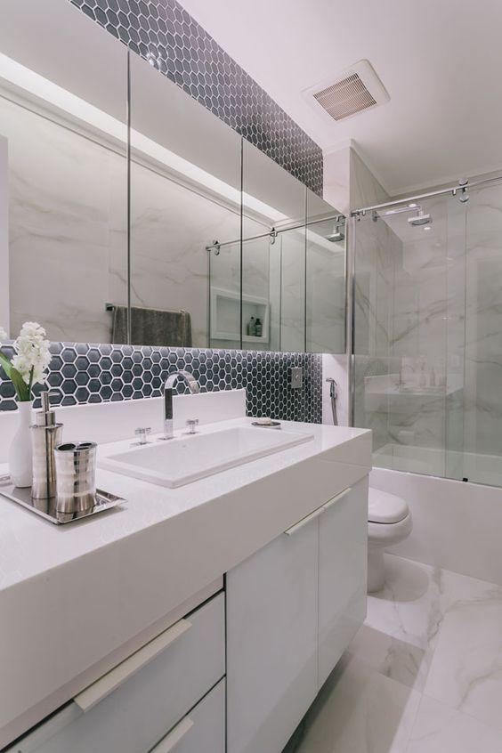 Banheiro pequeno com mármore e pastilha em azul.