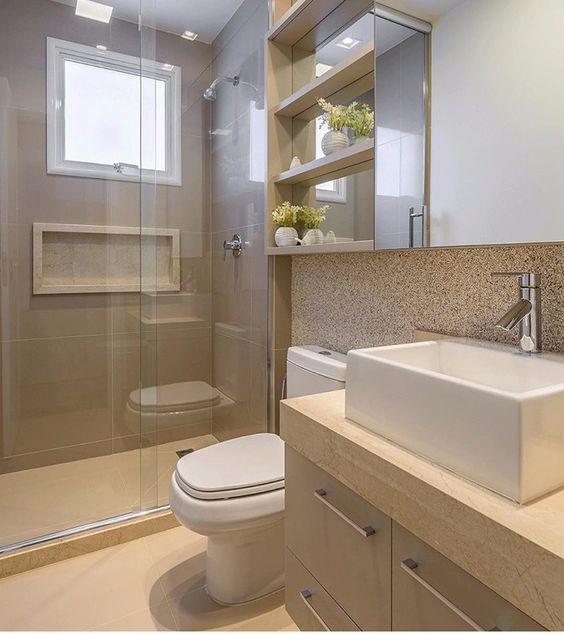 Banheiro pequeno e com armários planejados na cor creme.