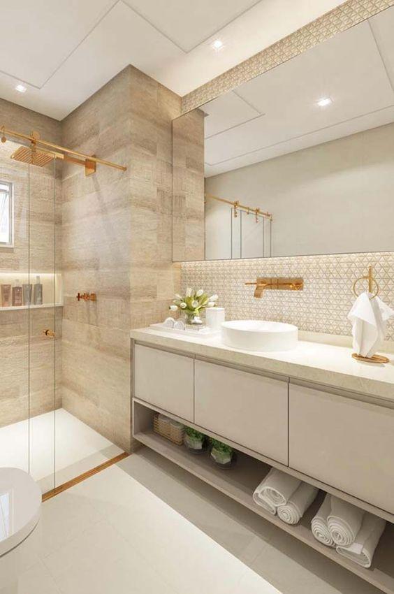 Banheiro planejado com armário claro, cuba sob o gabinete e metais dourados.