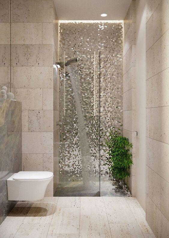 Banheiro planejado com revestimento em tom marrom e pastilhas brilhantes.