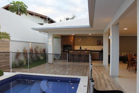 Área de lazer com piscina e cercado de vidro.
