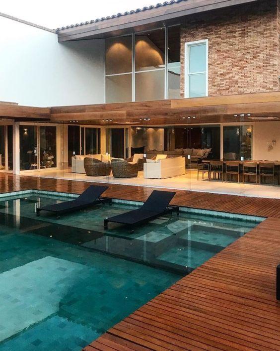 Área de lazer com piscina e espreguiçadeiras.