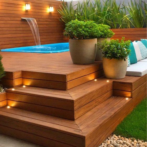 Área de lazer com piscina em deck de madeira