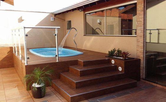 Área de lazer com piscina e parede de vidro.